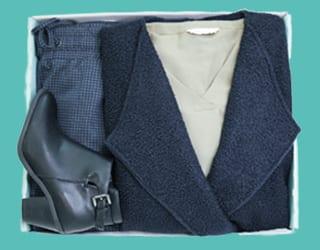 blaue Stickjacke, Boots, Bluse und gemusterte Hose
